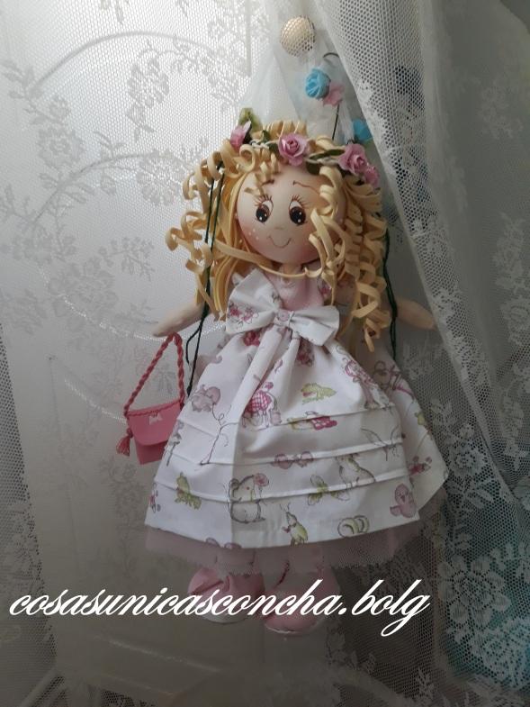 Fofucha en columpio con vestido y pololos de tela y cancan de tul, también tiene un bolsito