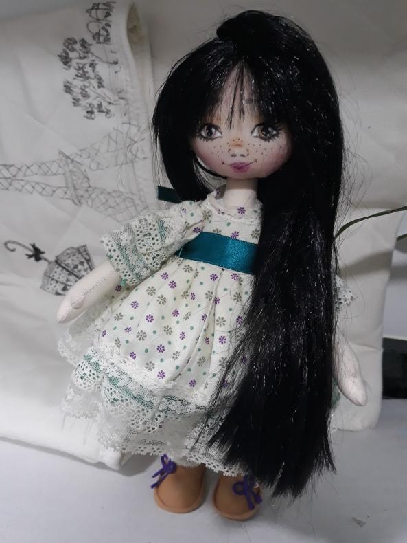 Muñeca de trapo, hecha a mano, con un par de pantalones campana para poderla cambiar, blusa zapatos a juego, vestido y calcetines con puntillas, pelo liso y largo negro sintético y una cara con pequitas.